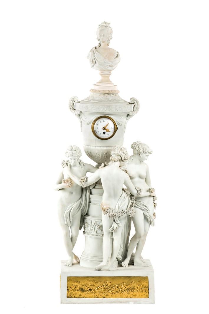 563 Reloj de sobremesa de biscuit de Sèvres y placas de bronce. Ffs. S. XIX. Marcas en la base. Estilo Luis XVI. Moldeado con Las tres Gracias inspiradas en la obra de Falconet.
