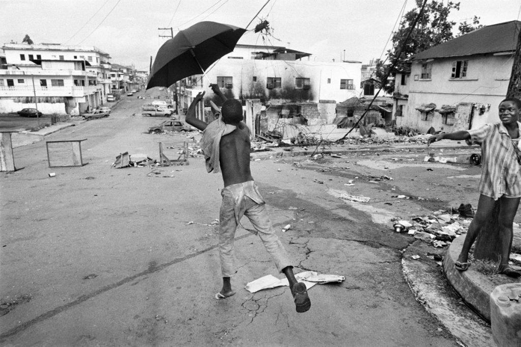 Un ni§o juega con un paraguas en la avenida principal destru°da por los combates