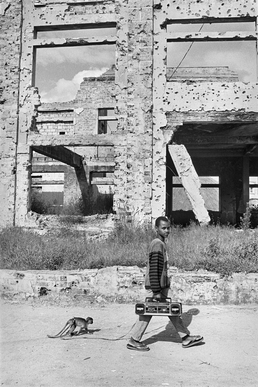 Un ni§o pasea a su mono entre las ruinas de su ciudad