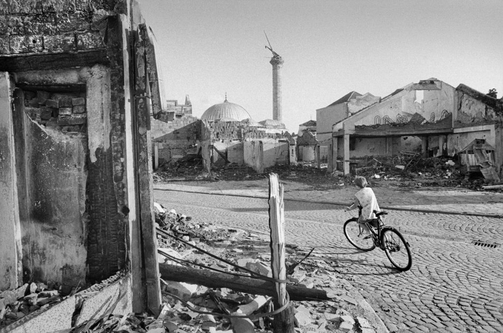 Una ni§a circula entre las ruinas de una ciudad