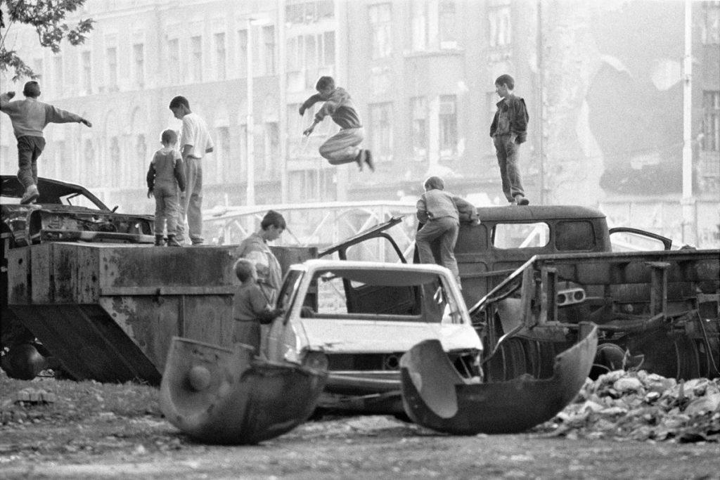 Varios ninos juegan entre coches y caminonetas destrozadas.