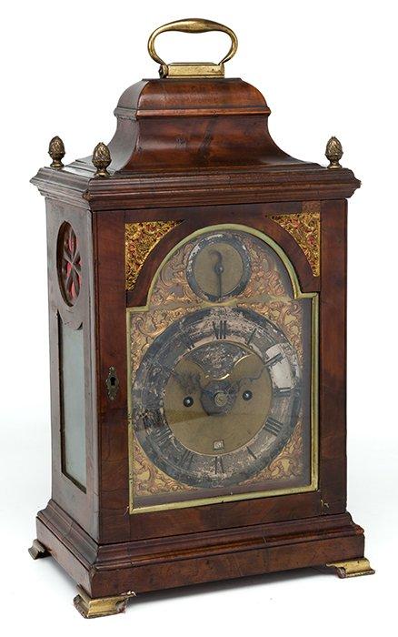 330 Reloj bracket inglés, S. XVIII, en madera de caoba, con aplicaciones en bronce dorado. Esfera en bronce, firmada Ralph Gout London, con maquinaria de dos trenes. Asas laterales.00