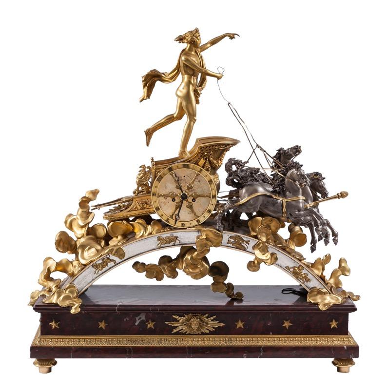284 Reloj de sobremesa rematado por Faeton y el carro del Sol de bronce dorado, cincelado y patinado sobre base de mármol rojo, trabajo francés S.XIX.00