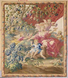 449-Tapiz-Aubusson,-Francia,-siglo-XVIII.-En-lana.-Con-representación-de-escena-con-ninfa-y-niños-Baco.-Cenefa-con-encintados-y-flores